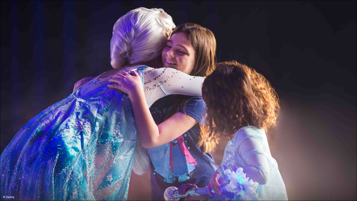 Elsa hugging a little girl in the audience