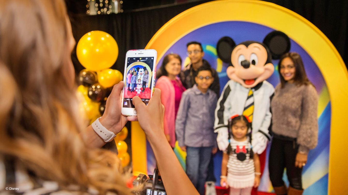 Woman taking a group photo of mickey mouse and audience members