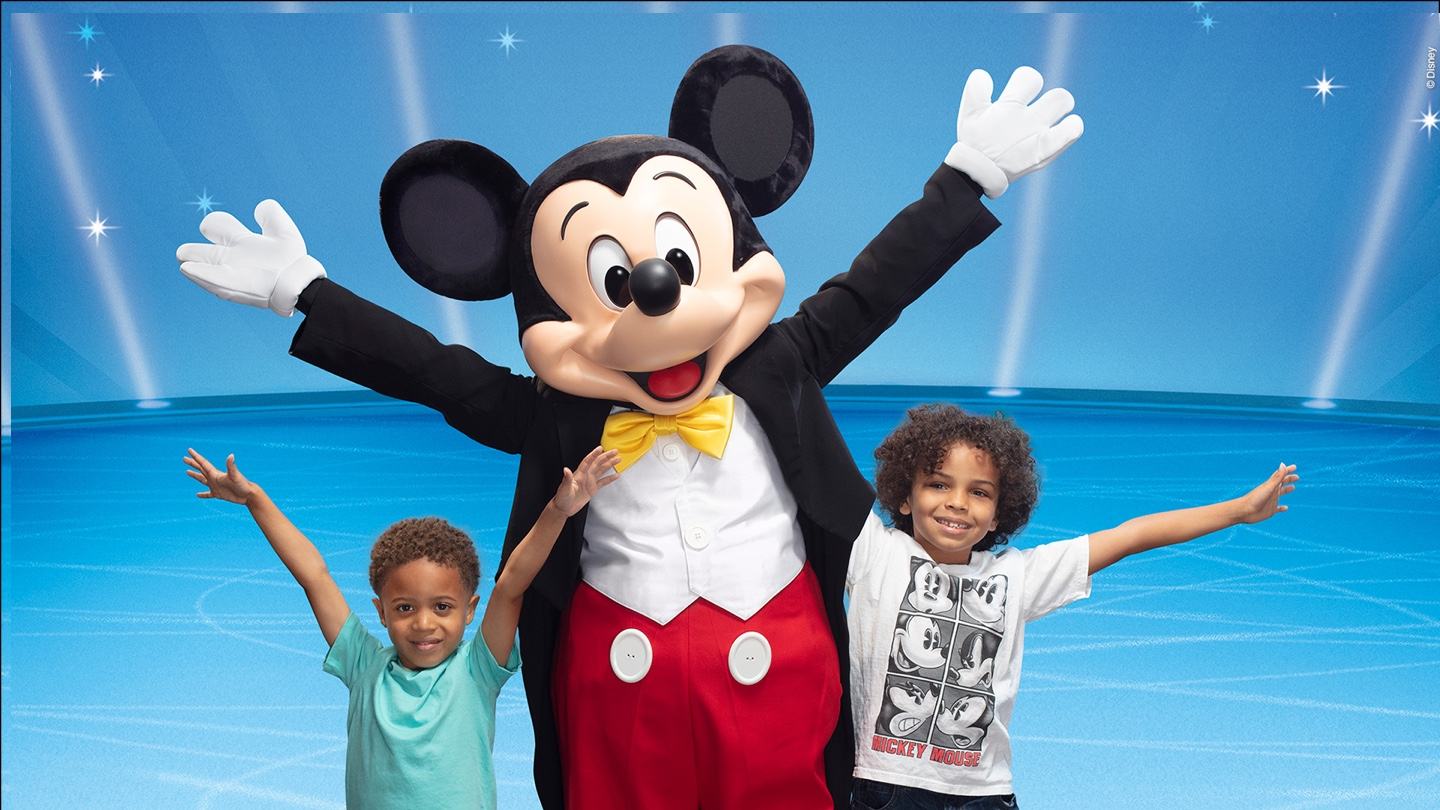 Mickey mouse posing for a picture with two young boys