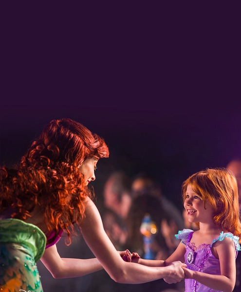 Arial holding a young girls hands during a show