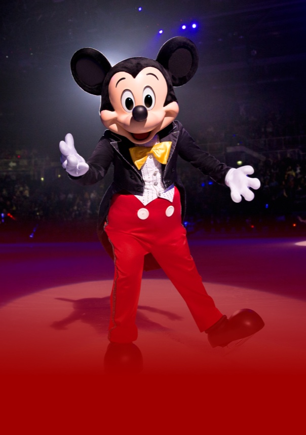 Mickey Mouse standing on stage with his hands out
