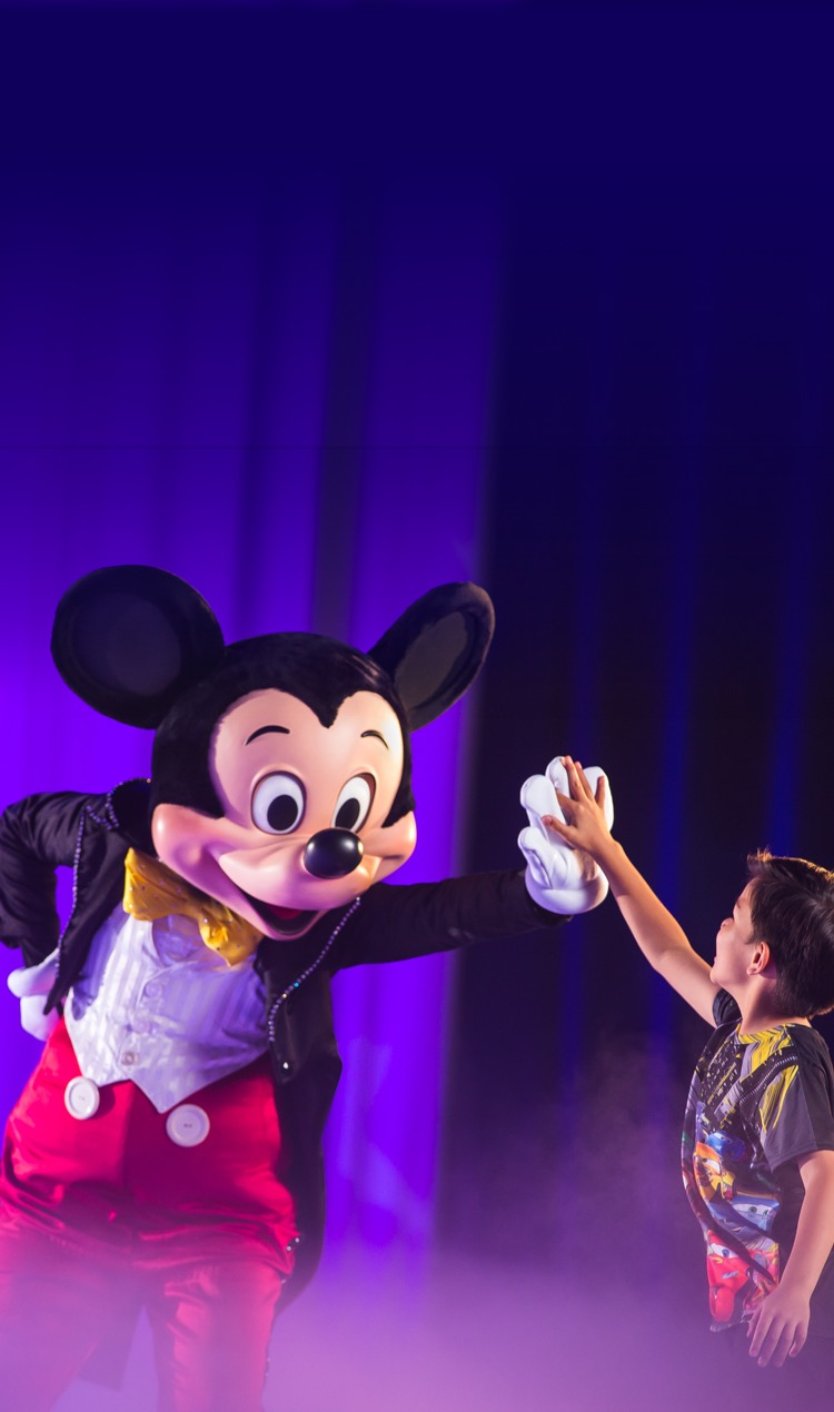Mickey Mouse high fives a young boy