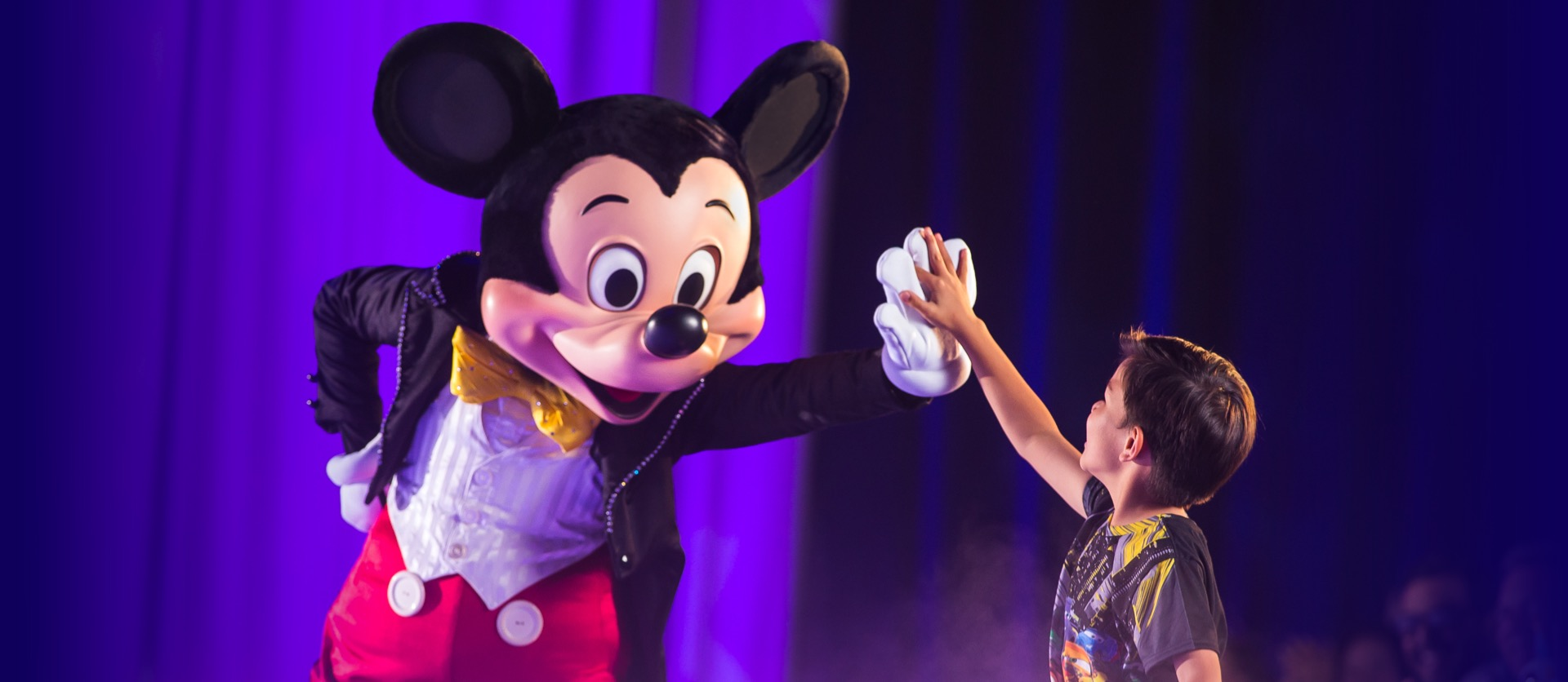 Mickey Mouse highs fives boy in from the crowd