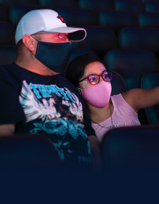dad and daughter wearing masks and enjoying the show